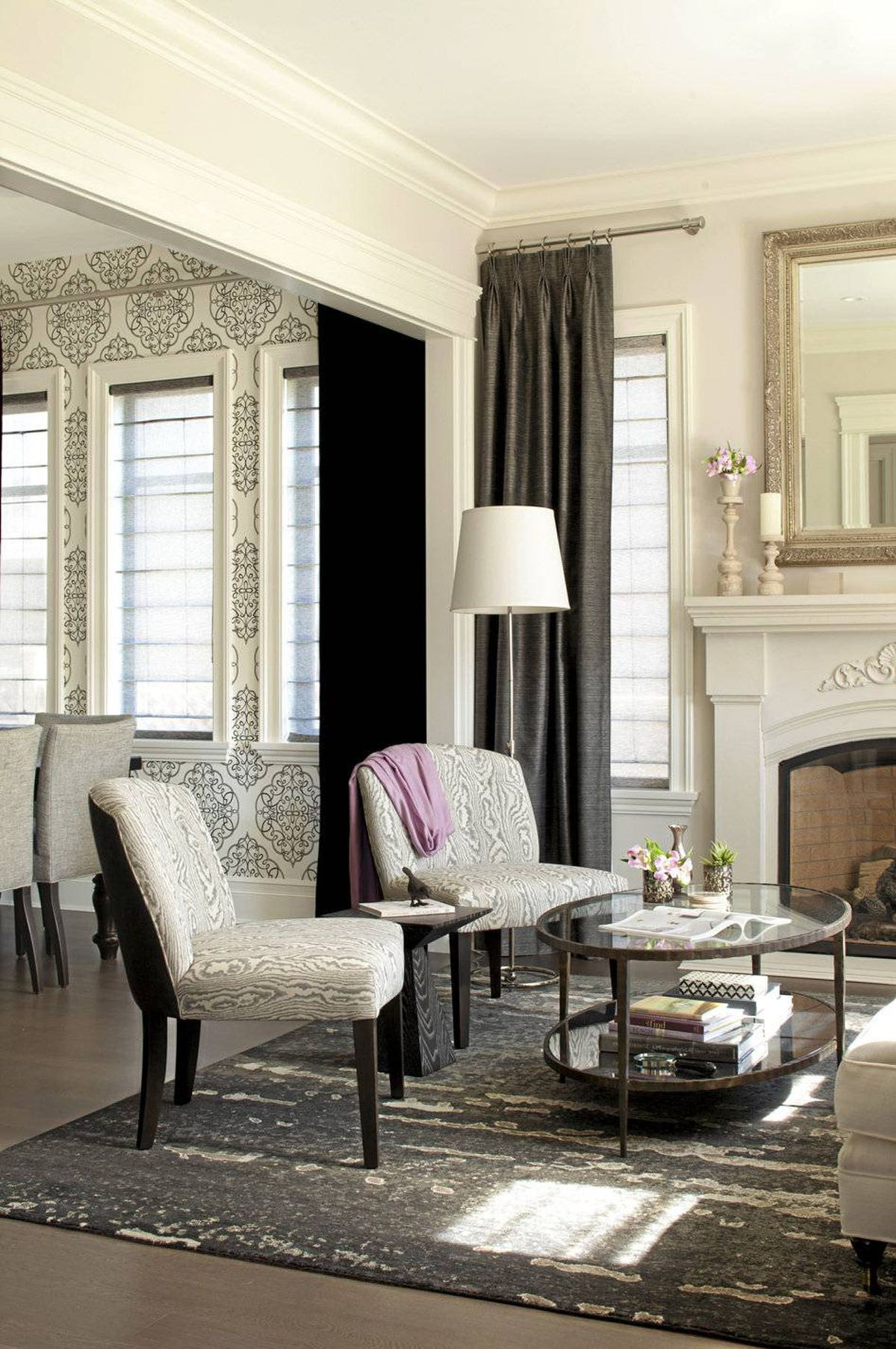Identical, custom-built slipper chairs, upholstered in grey and white on the front side, and midnight linen on the black. From the living room, the pattern on the chairs adds visual intrigue to the space.