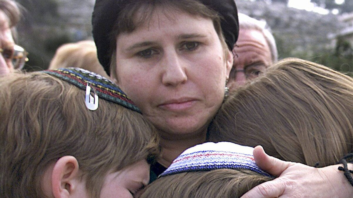 The children of slain settler Shmuel Gillis are embraced by their mother Ruti Gillis, on Feb. 2, 2001, at the site where their father was killed in a drive-by shooting near Hebron on his way home to the Jewish settlement of Carmei Tzur in the West Bank.