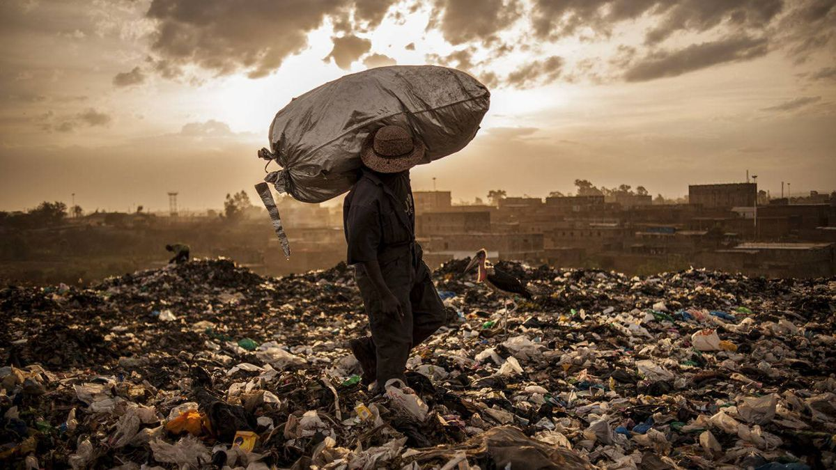 A man from the neighboring slum of Korogocho , Kenya hefts his last bag of trash for the day in Dandora city dump in hopes of selling the mostly rubber scraps for 50 cents.