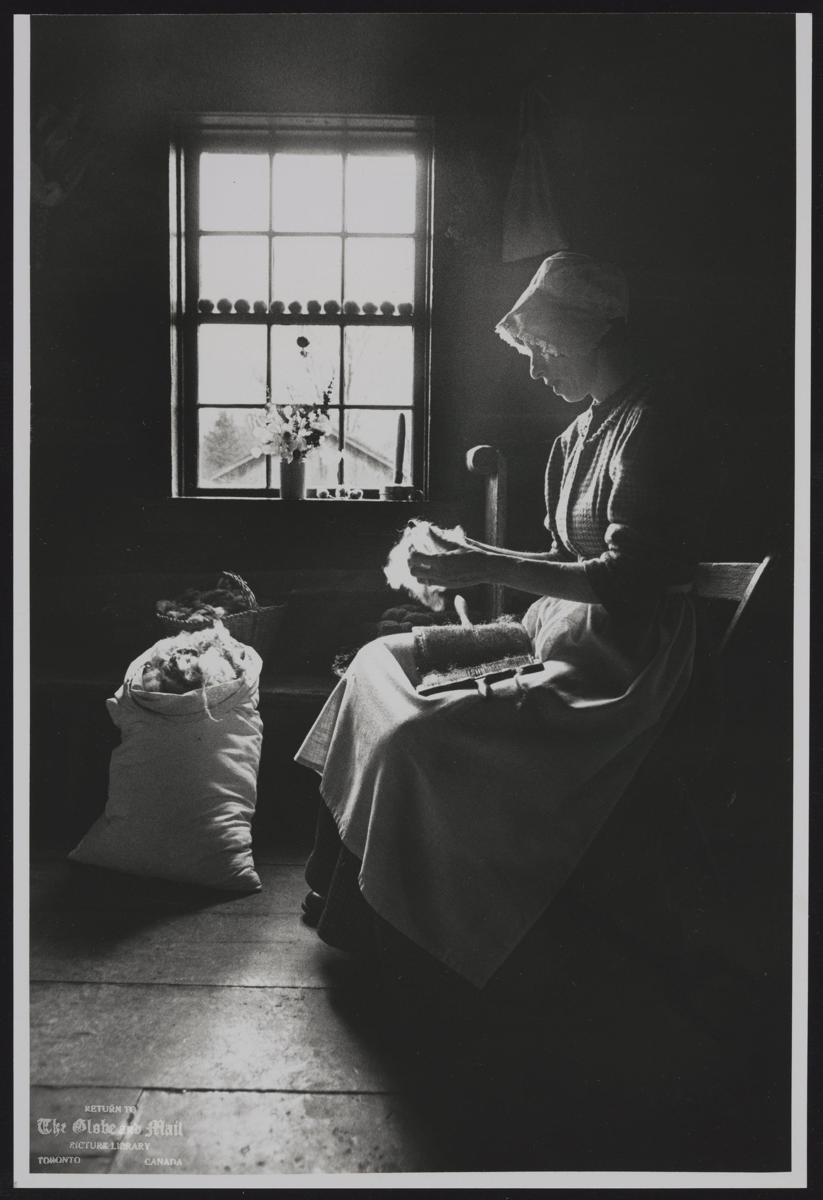 The notes transcribed from the back of this photograph are as follows: Kate Shapero, an historical interpreter at Black Creek Pioneer Village prepares wool for making Christmas decorations