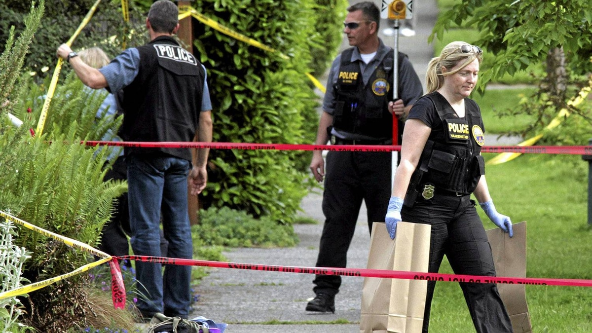 Seattle Police Department crime scene investigators collect evidence from a crime scene in a West Seattle neighborhood where a gunman shot himself after being confronted by police in Seattle, Washington May 30, 2012. The gun the gunman used to shoot himself is at the lower left of photo near the yellow number 1 and number 2 markers. Earlier in the day the gunman shot two men and a woman to death at a popular Seattle cafe, then fled to a downtown parking lot, where he fatally shot another woman and stole her car.