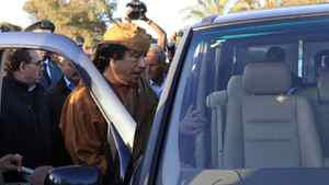 Libyan leader Moammar Gadhafi gets into his car in the compound of Bab Al Azizia in Tripoli, after a meeting with a delegation of five African leaders seeking to mediate in Libya's conflict, April 10, 2011.