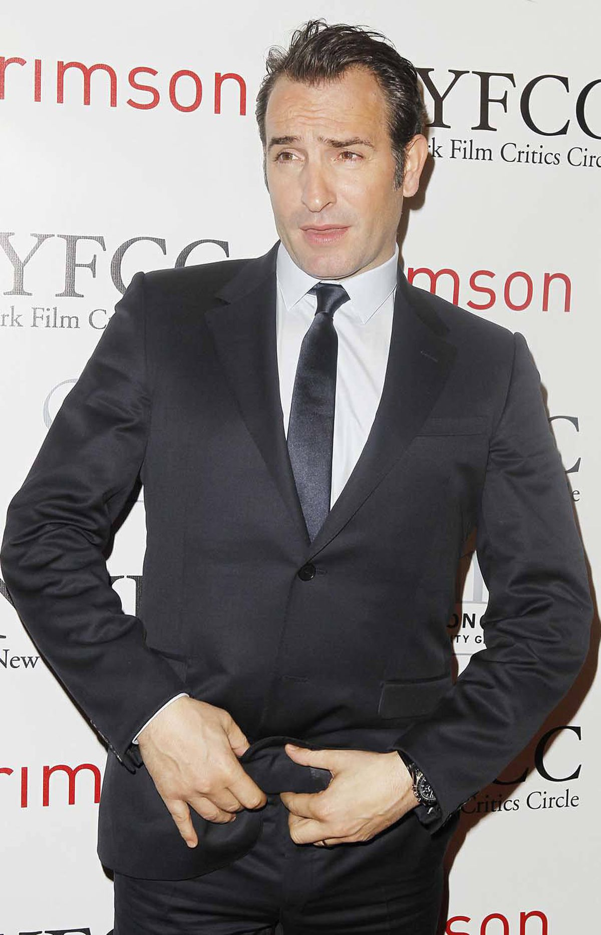 """Jean Dujardin, star of the silent film """"The Artist,"""" deals with what one hopes is a wardrobe malfunction on the red carpet at the New York Film Critics Circle Awards on Monday."""