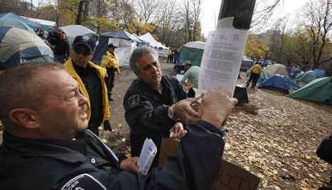 City of Toronto By-Law officers escorted by Toronto Police service post an eviction and trespass notice on a poll in the Occupy Toronto Camp at St. James Park in Toronto Tuesday, November 15, 2011.