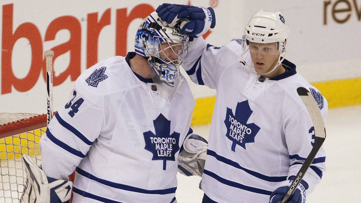 Toronto Maple Leafs netminder James Reimer is congratulated by teammate Carl Gunnarsson (right) following the final whistle as the Leafs defeated the Ottawa Senators 5-3 during NHL pre-season action in Ottawa, Tuesday September 27, 2011.