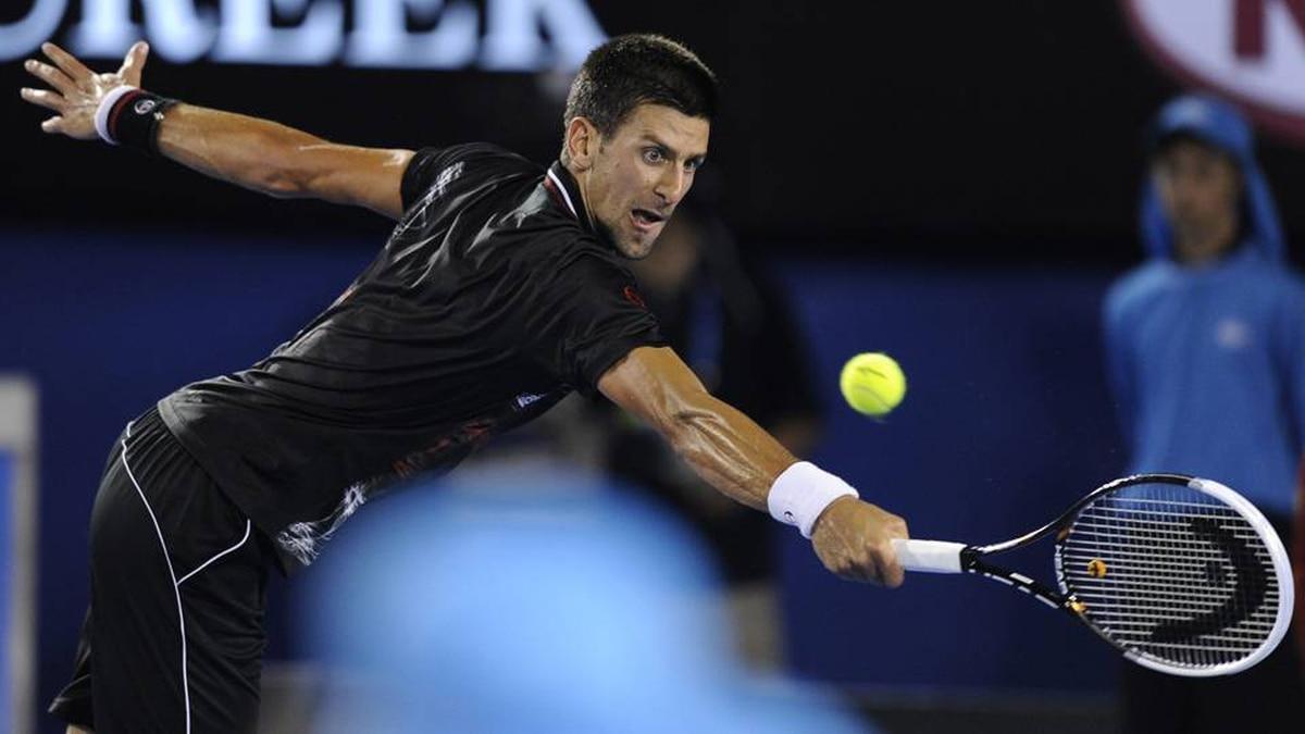 Novak Djokovic of Serbia makes a return to Lleyton Hewitt of Australia during their fourth round match at the Australian Open tennis championship, in Melbourne, Australia, Monday