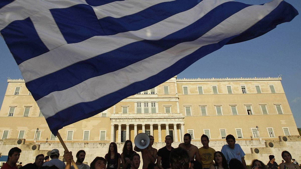 Protesters raise a Greek flag in front of parliament during a rally against austerity economic measures in Athens' Syntagma (Constitution) Square in this June 17, 2011 file photo.