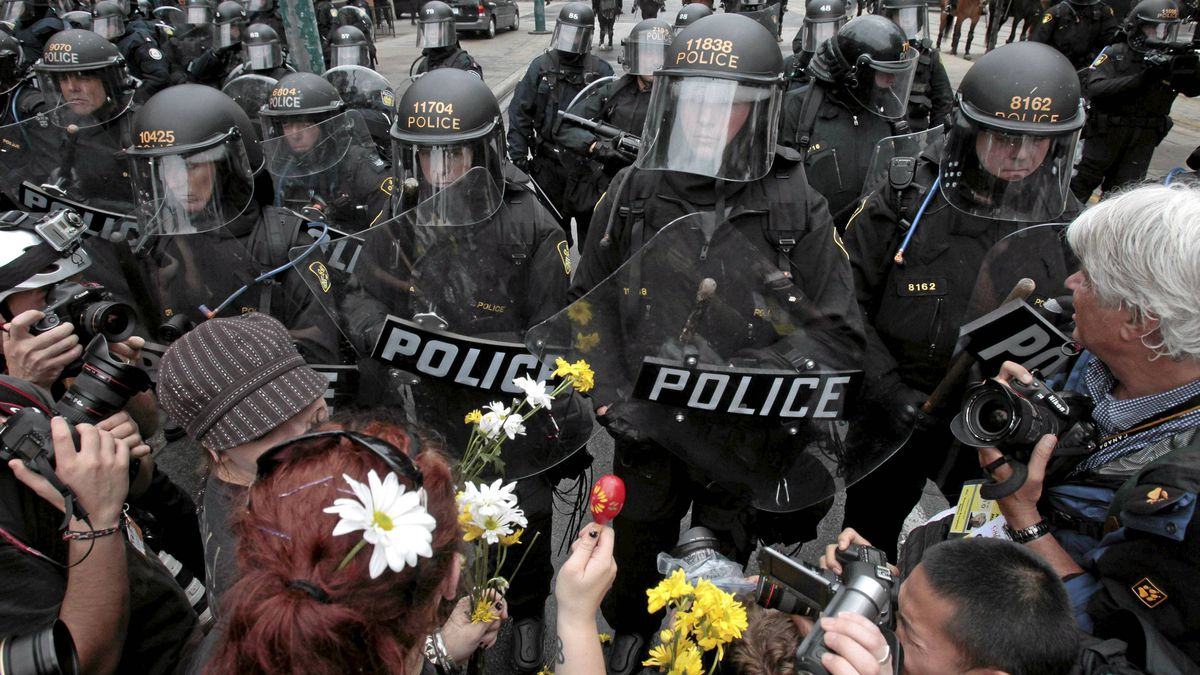Demonstrators with flowers face riot police during protests ahead of the G20 summt in Toronto June 26, 2010.