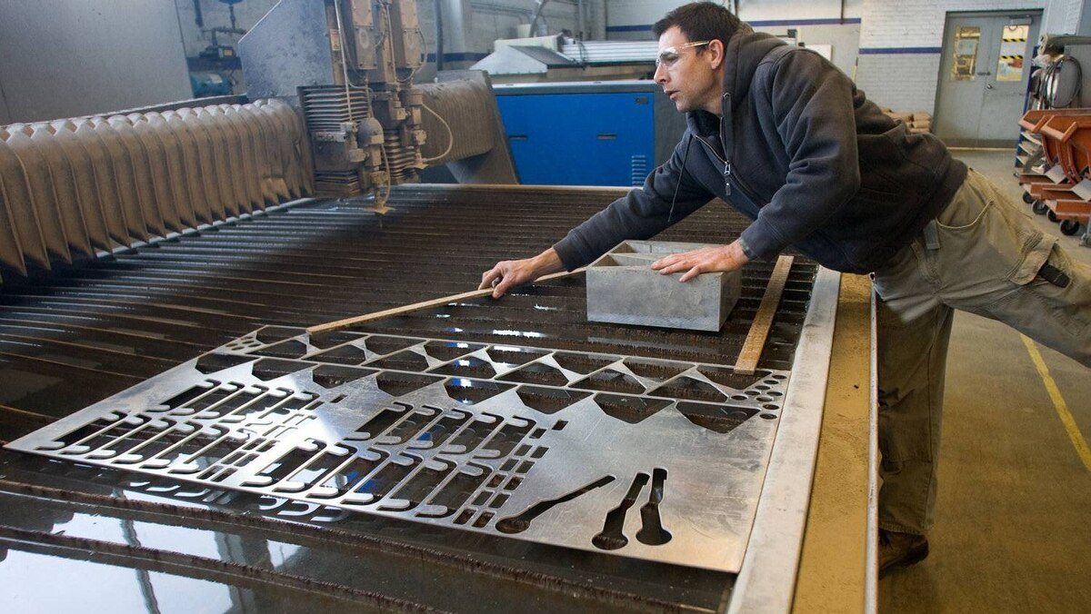 Greg Watson removes metal from a water cutter used to make precision cuts in various types of steel.
