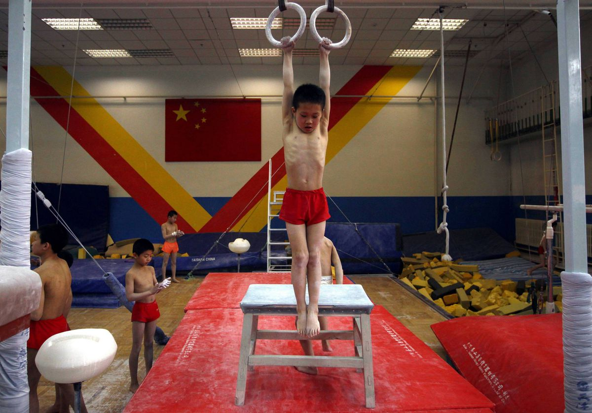 A young gymnast steps off a table used to reach gymnastic rings during a gymnastics class.