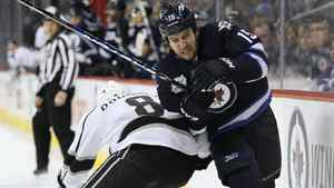 Winnipeg Jets forward Tanner Glass (15) is checked by Los Angeles Kings defenceman Drew Doughty (8) during second period NHL action in Winnipeg on Thursday, December 29, 2011.