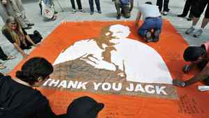 People pay their respects as they write messages on the sidewalks and a banner remembering late NDP leader Jack Layton at Toronto City Hall on Aug. 26, 2011.