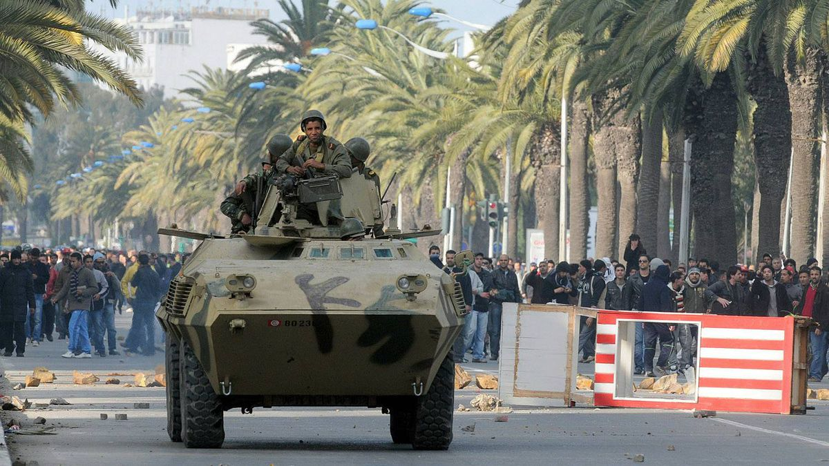 Soldiers on an armoured vehicle stand in front of demonstrators on Mohamed V avenue in Tunisia on Jan. 14, 2011.
