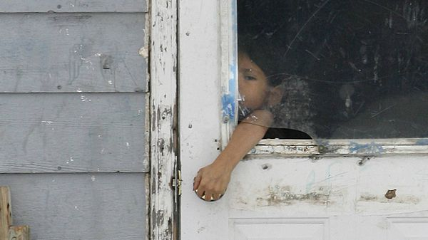 A child reaches through a broken window to open the door of a house on the Pikangikum First Nation, in January, 2007. At the time, half of the community's 430 homes were unfit to live in, yet continued to be occupied. Ninety per cent didn't have running water or indoor toilets.