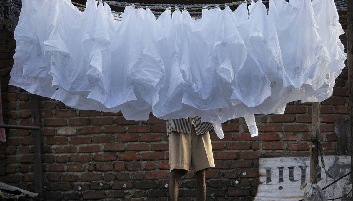 A laundryman hangs washed clothes to dry at the Dhobi Ghat open air laundry in Mumbai.