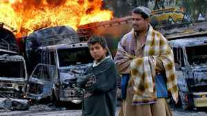 Bystanders pose in front of Afghanistan-bound NATO oil tankers set on fire by militants at the Pakistani border post of Torkham on March 4, 2011.