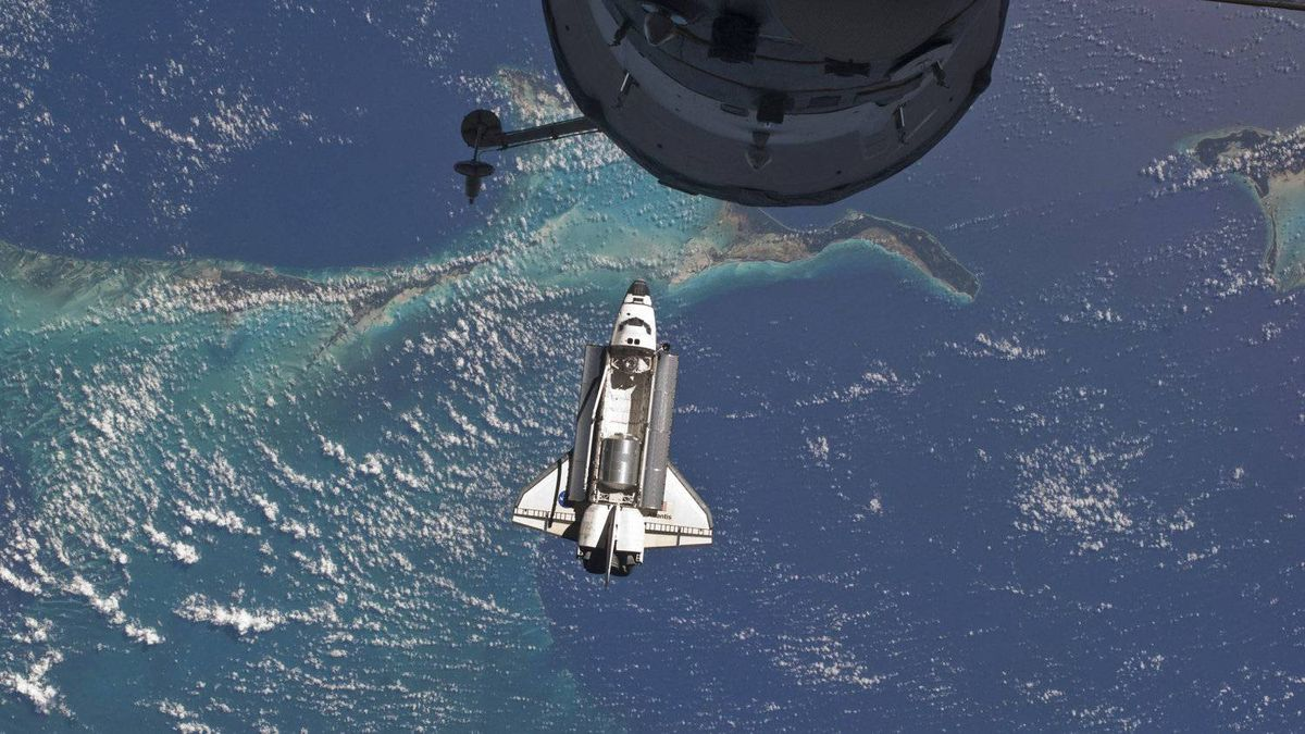 In this Sunday, July 10, 2011 photo provided by NASA, the space shuttle Atlantis is seen over the Bahamas prior to a perfect docking with the International Space Station. Part of a Russian Progress spacecraft which is docked to the station is in the foreground.