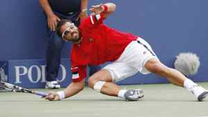 Janko Tipsarevic of Serbia falls to the court after returning a shot from Juan Carlos Ferrero of Spain. Tipsarevic advanced with a 7-5, 6-7 (3), 7-5, 6-2 victory. REUTERS/Jessica Rinaldi