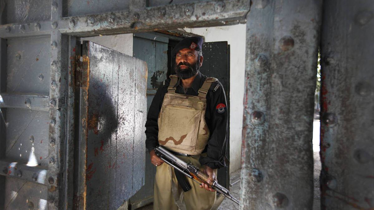 A police officer stands guard May 8, 2011, at the gates of Abbottabad's central police station, where officials announced recently that foreign guests cannot stay in hotels without written permission and should remain off the streets at night.