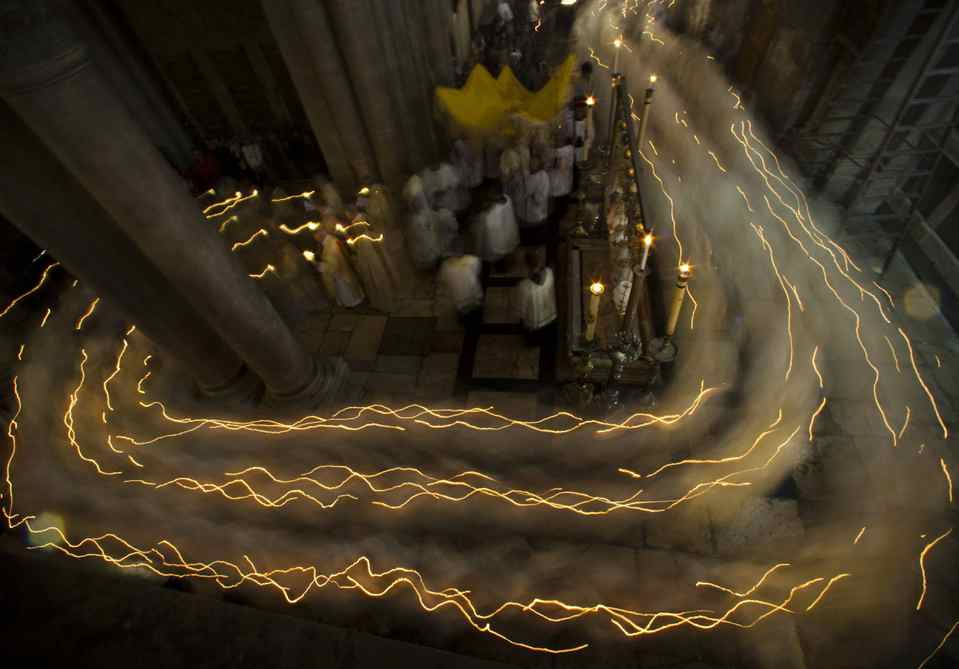Catholic clergy walk holding candles during the Holy Thursday procession of the Washing of the Feet inside the Church of the Holy Sepulchre, traditionally believed to be the burial site of Jesus Christ, in Jerusalem's Old City, Thursday, April 5, 2012.