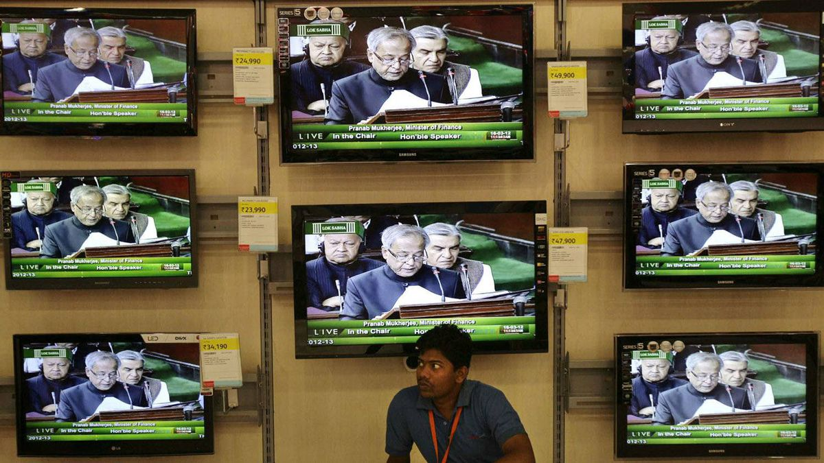 An Indian man sits in front of television screens broadcasting coverage of Indian Finance Minister Pranab Mukherjee as he reads out the budget, at a store in Bhubaneswar, India, Friday, March 16, 2012.