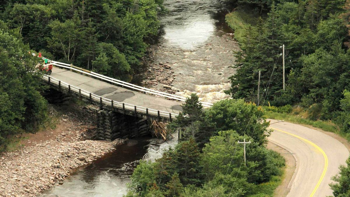 People stand on one side of a closed bridge that leads to the community of Meat Cove on Cape Breton. Paul Darrow for The Globe and Mail