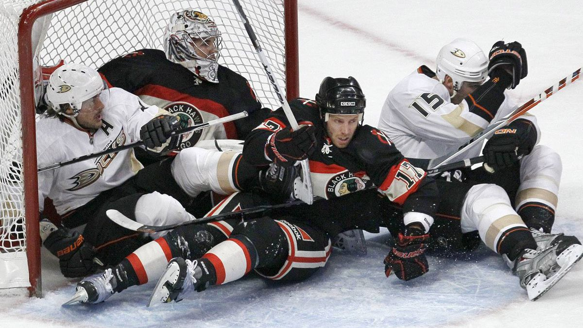 Several players, from left, Anaheim Ducks right wing Teemu Selanne, Chicago Blackhawks goalie Corey Crawford, Blackhawks' Ryan Johnson, and Ducks' Ryan Getzlaf, slide into the goal, during the second period of their NHL hockey game Saturday, March 26, 2011 in Chicago. The Ducks won 2-1. (AP Photo/Charles Rex Arbogast)