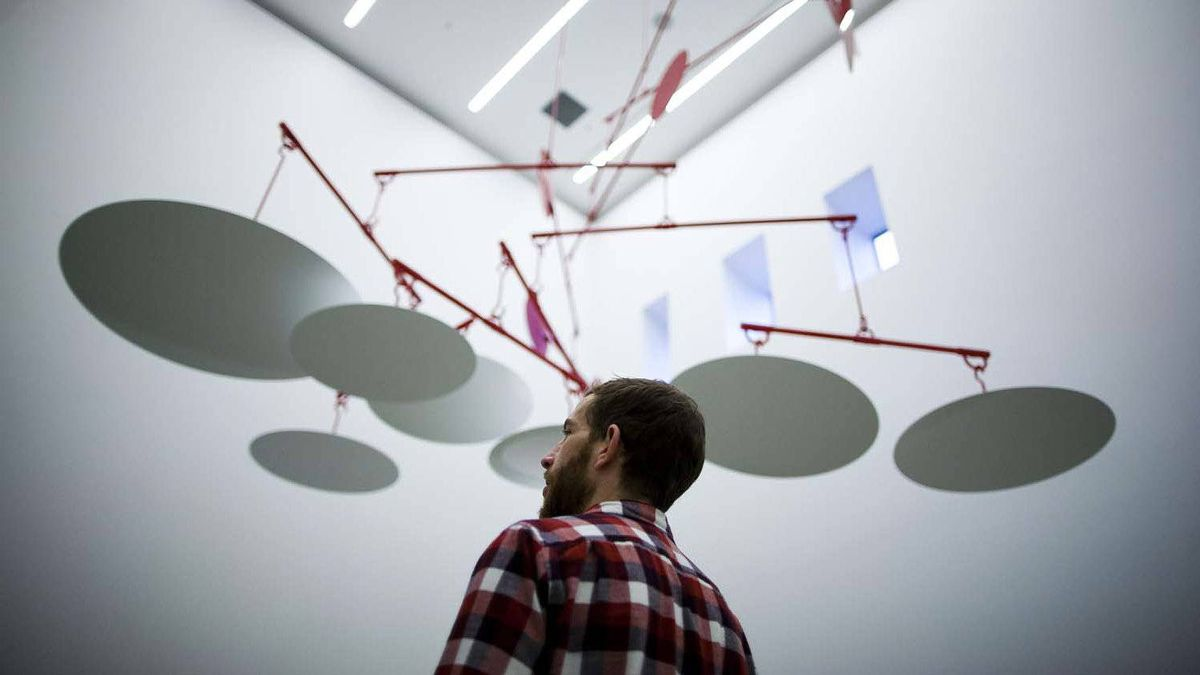 """Damian Moppett stands underneath his mobile installation """"Broken fall"""" at the Rennie Collection at Wing Sang in Vancouver."""