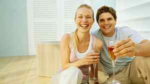 Young couple celebrating their new home with champagne