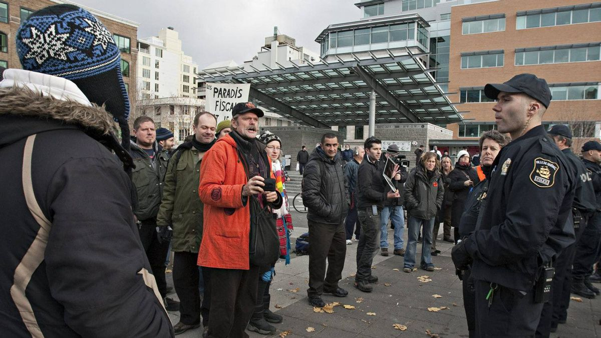 Occupy Quebec demonstrators face police officers after city workers dismantled a temporary building, Friday, November 18, 2011 in Quebec City.