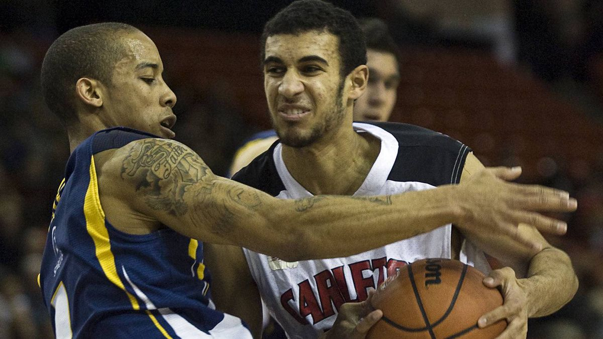 Carleton Ravens Philip Scrubb drives past Trinity Western Spartans Tristan Smith in CIS Final 8 men's basketball championship action in Halifax, March 13, 2011.