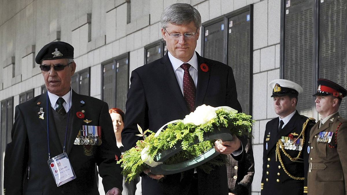 Prime Minister Stephen Harper carries a wreath while escorted by a Canadian war veteran at the National War Memorial, during a Remembrance Day service in Seoul Nov. 11, 2010.