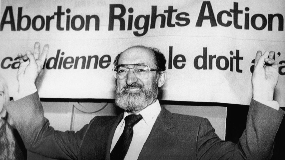"Dr. Henry Morgentaler stands in front of banner which reads, ""Canadian Abortion Rights Action League,"" in 1988."
