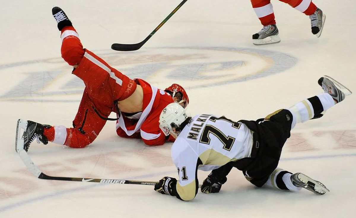 Evgeni Malkin of the Pittsburgh Penguins collides with Darren Helm of the Detroit Red Wings.