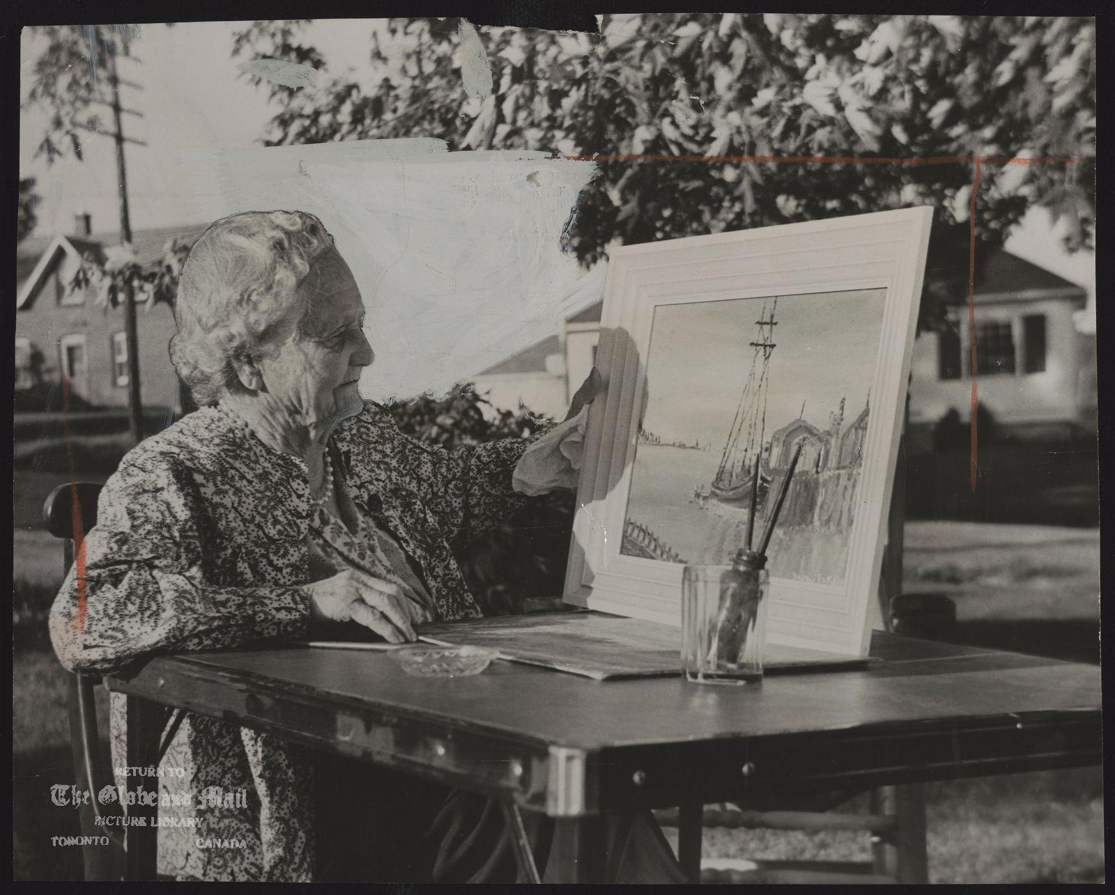 In her Burks Falls garden, Grandma Parker studies seacoast scene she painted [Mrs. Naomi Ada Parker, artist]