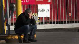 A laid off Aveo employee makes a call in front of the aircraft maintenance company's plant Tuesday, March 20, 2012 in Montreal.THE CANADIAN PRESS/Ryan Remiorz