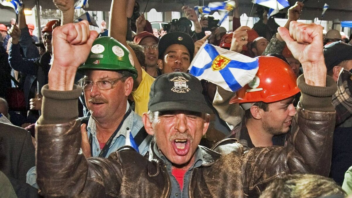 Workers react after Ottawa's announcement that the Irving-owned Halifax Shipyard is getting a $25-billion contract to build Canadian combat ships on Oct. 19, 2011