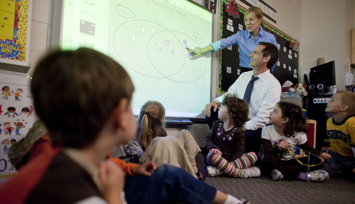 Premier Dalton McGuinty is instructed on the use of a smart-board by kindergarten teacher Jennifer Lefteris during a visit to the new full day kindergarten classes at Stoney Creek Public School in London, Ontario, October 8, 2010.