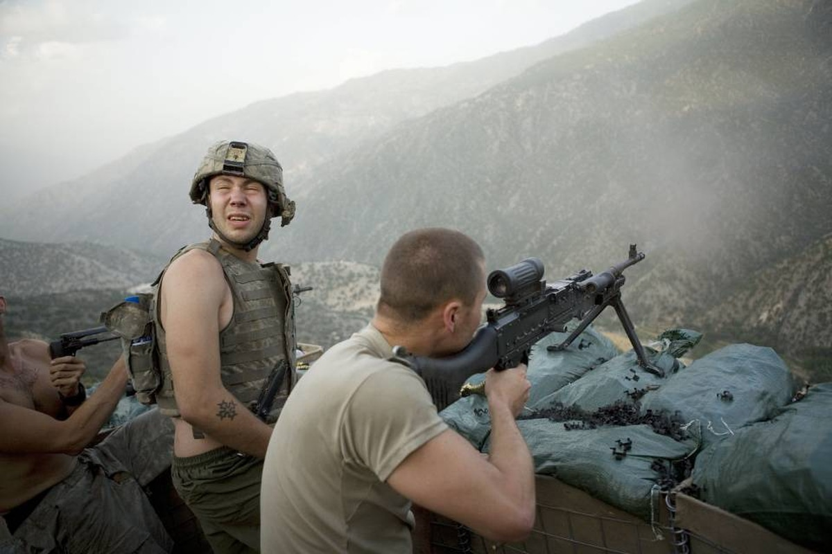 Misha Pemble is startled by the sound of gunfire during a firefight across the valley with insurgents.
