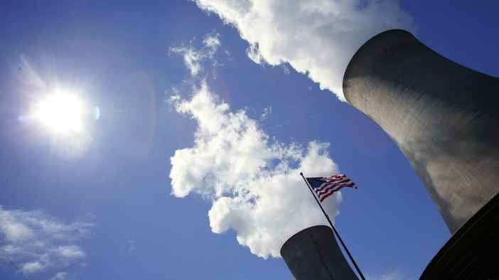 A U.S. flag flutters in front of cooling towers at the Limerick Generating Station in Pottstown, Pennsylvania May 24, 2006.