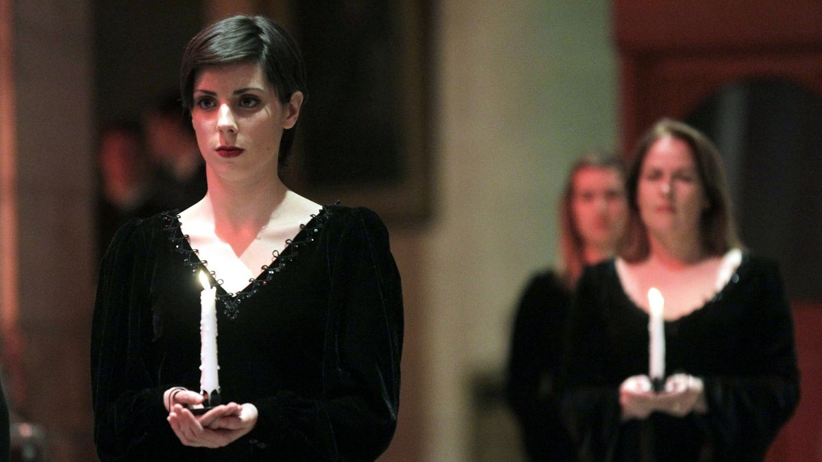 Women hold candles during a Titanic commemoration service at St. Ann's Cathedral in Belfast on Saturday.