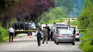 RCMP officers gather at the scene where murder suspect Angus David Mitchell was shot by officers in rural Maple Ridge, B.C., before dying in hospital on Wednesday May 30, 2012. Mitchell was killed in a confrontation that came a few hours after they had issued a public warning, saying that he was armed and dangerous, and was being sought in three shooting incidents that left two people dead.