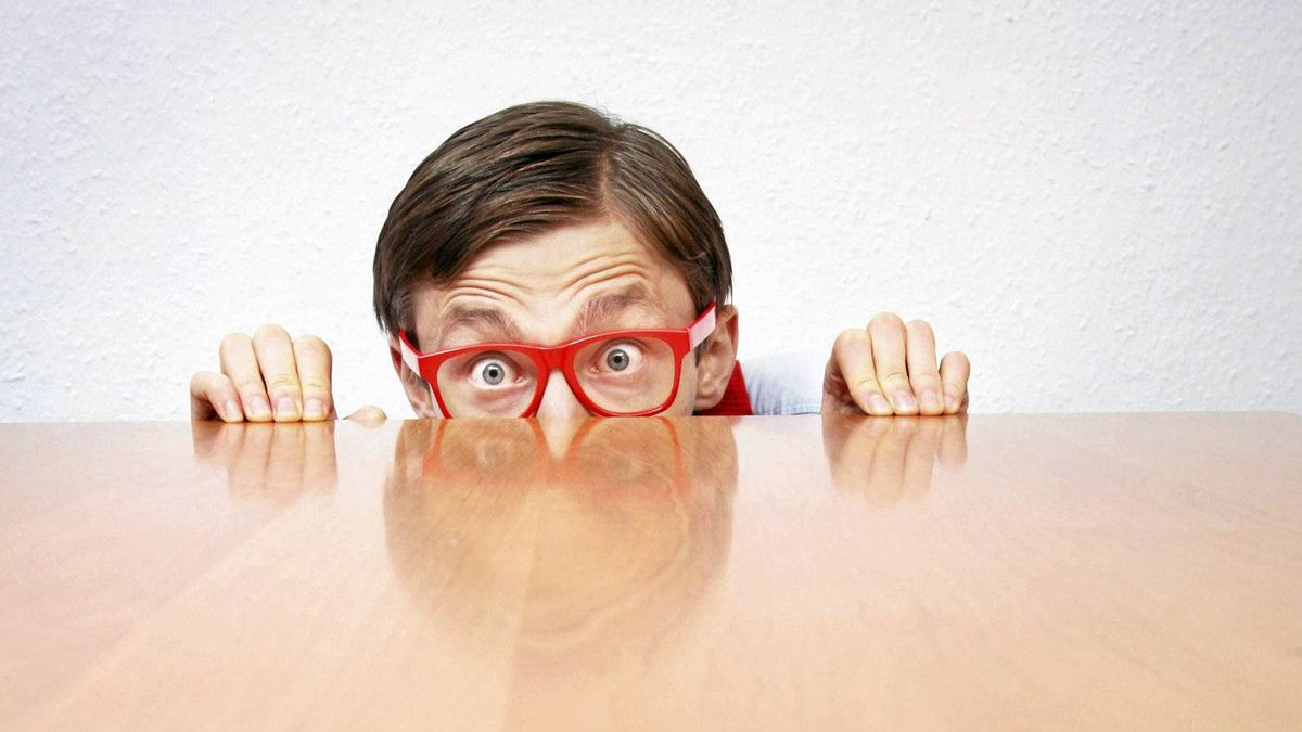 Scared nerd hiding behind a desk.