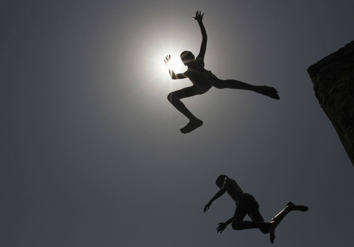 Boys dive into the sea at a fishing harbour to cool themselves on a hot day in the southern Indian city of Chennai.
