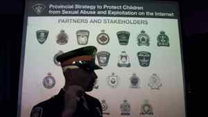 A police officer walks past a projection of the Ontario Police services that participated in a province-wide investigation targeting child pornography offenders following a media conference in Vaughan, Ontario on Thursday, February 2, 2012.