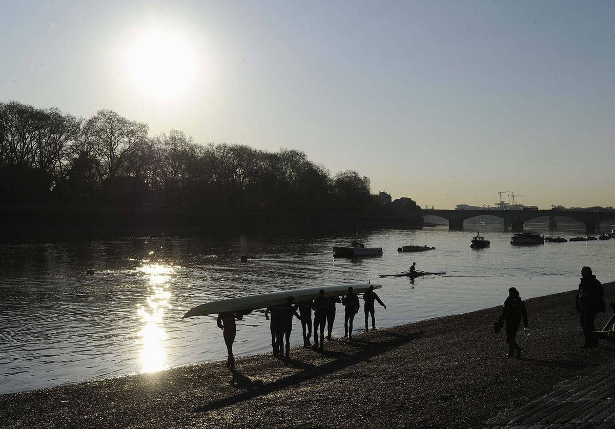 Members of the Oxford University rowing crew carry their boat into the River Thames in west London. The rowing crews from Oxford and Cambridge will compete in the 158th Boat Race between the two universities on Saturday.