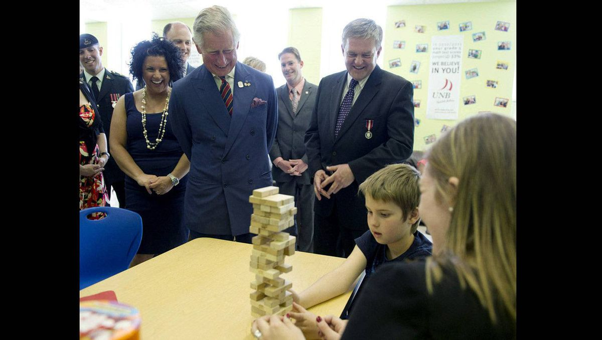 Prince Charles and New Brunswick Premier David Alward watch a boy and his mother play Jenga while touring the Hazen White-St Francis School in Saint John, N.B., on Monday, May 21, 2012. The royal couple are on a three-day visit to Canada to mark the Queen's Diamond Jubilee.