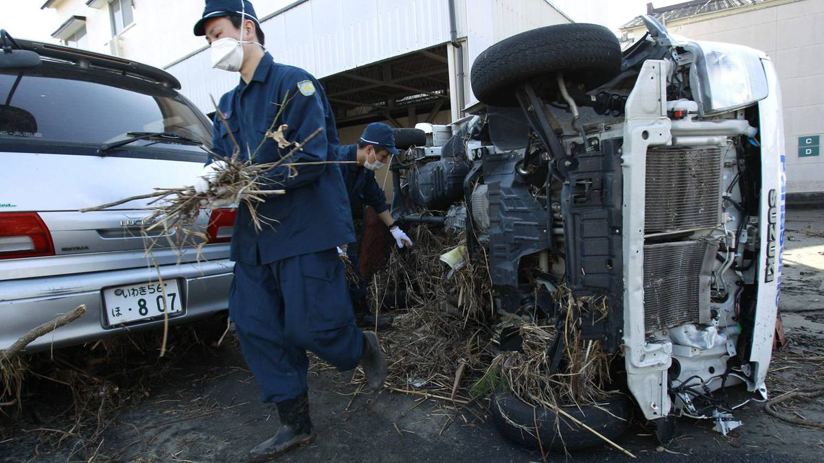 Police officers in Iwaki city, Fukushima prefecture, Japan, start to clean debris from tsunami waters following Friday's massive earthquake, Sunday, March 13, 2011.