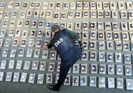 Colombian intelligence services officer arranges packages of cocaine in Cali