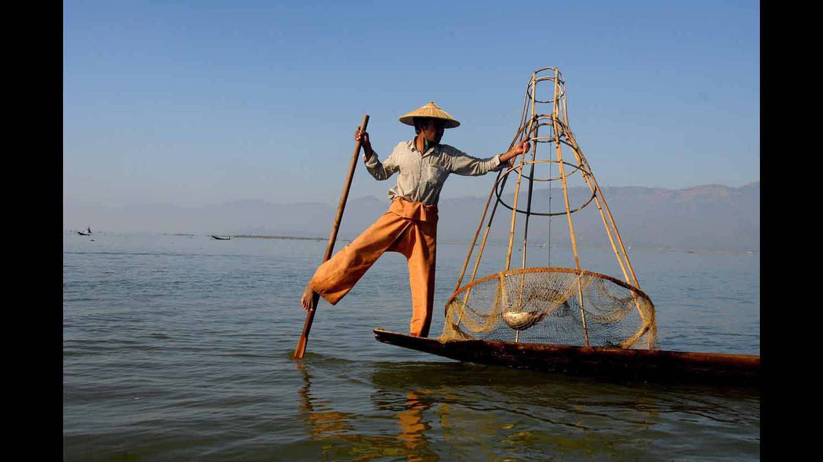 A fisherman employs a technique unque to Burma, using his feet to paddle and a drop net to trap the day's catch